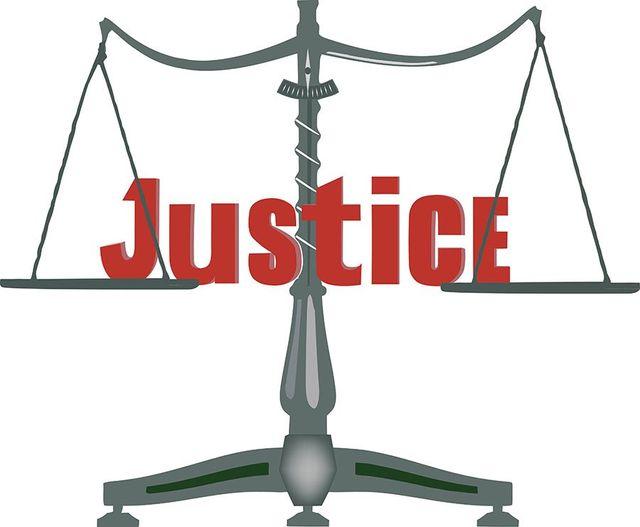 una bilancia a due piatti e la scritta Justice