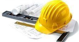 un casco antinfortunistico, un metro  e dei disegni di costruzione