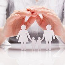 hands protecting a paper cut family