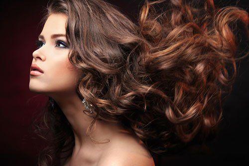 Donna con capelli castani,ricci e con riflessi