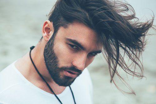 Giovane con barba accudita e moderno taglio di capelli
