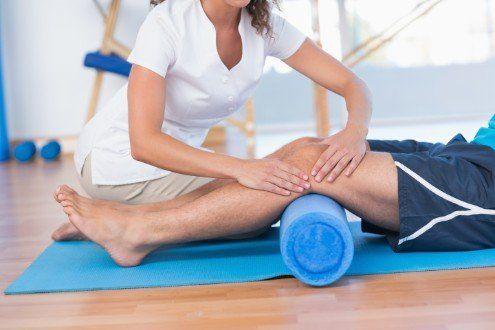 due mani di una fisioterapista che massaggiano il ginocchio di un uomo in palestra