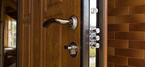 Acciaio nuovo porta tre chiavistello installato sulla porta d'ingresso in legno di una casa nuova costruzione che mostra i tre cilindri individuali della serratura