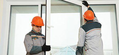 Due maschi lavoratori dei costruttori industriali di installazione finestra