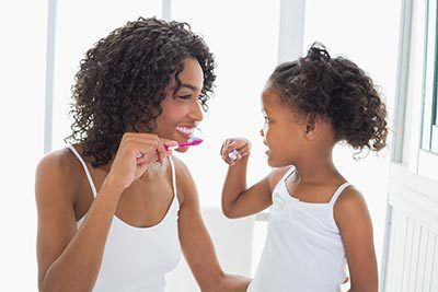 A mother and daughter brushing their teeth together in Cincinnati