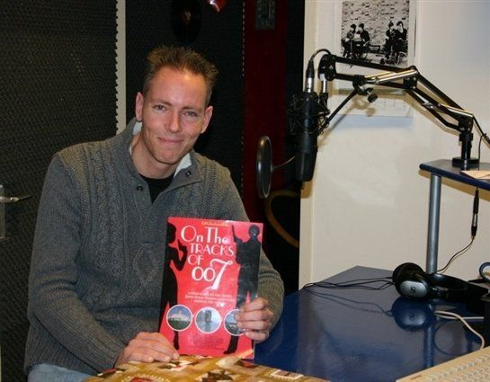 Martijn Mulder posing with his book 'On the gtracks of 007' in a radio studio