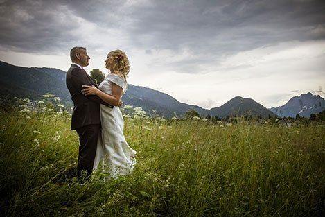 Coppia di sposi in un prato con montagne alle loro spalle