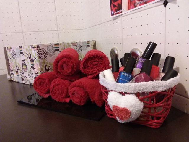degli asciugamani rossi arrotolati e un cestino con dei cosmetici