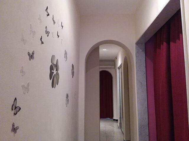 un corridoio con muri rosa e delle farfalle disegnate