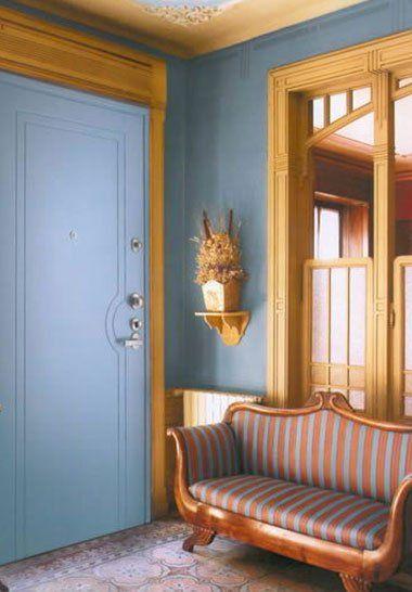 un divano di legno e sulla destra una porta di color azzurro