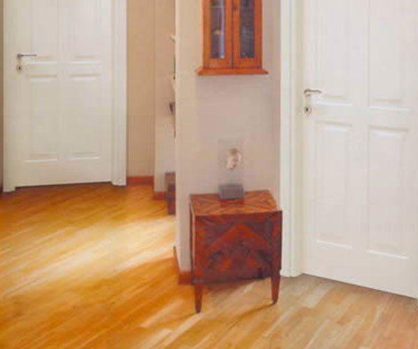 due porte in legno di color bianco e pavimento in parquet