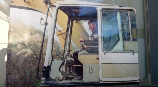 Un uomo sorridente nella cabina di un escavatore