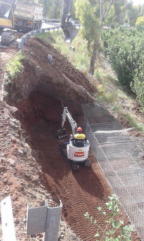 un uomo su una miniscavatrice in uno scavo
