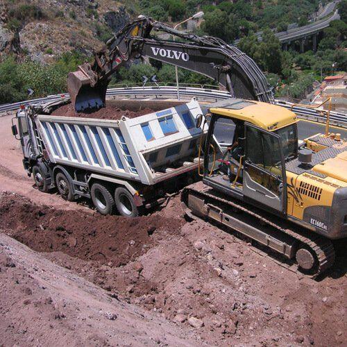 una scavatrice mette terra nel rimorchio di un camion