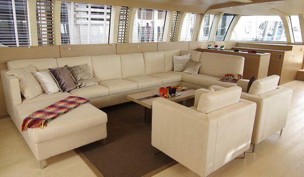 un salotto da yatch con un divano beige di pelle con penisola con di fronte due poltrone dello stesso colore e al centro un tavolino