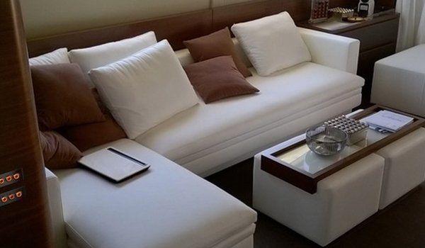un divanetto bianco angolare da yatch con dei cuscini marroni e bianchi e di fronte due pouf di pelle bianca che sorreggono un tavolino di legno e vetro con sopra degli oggetti