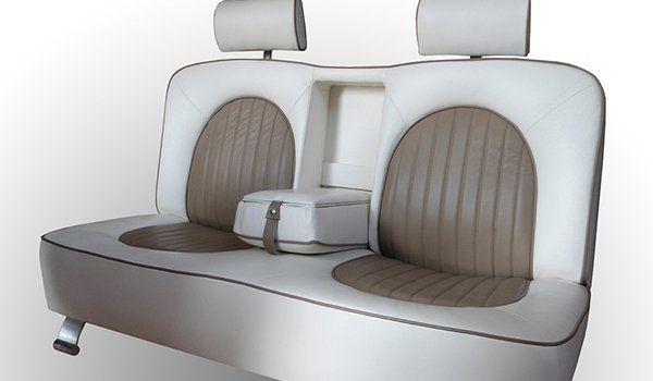 un sofà a forma di due sedili in pelle color panna e marrone con in mezzo un bracciolo