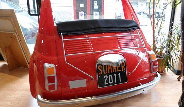 un divanetto a forma di Fiat 500 vecchio modello di color rosso vista da dietro con la targa con scritto Summer 2011