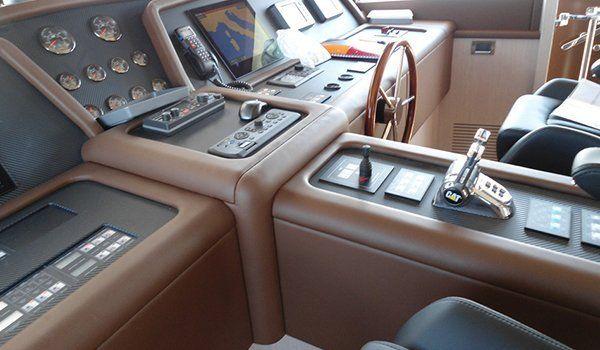 una cabina di pilotaggio con strumenti di navigazione, volante e un bracciolo al centro, il tutto rivestito in pelle marrone