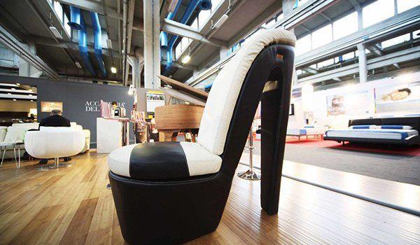 una poltrona a forma di scarpa con il tacco in pelle bianca e nera in un salone di esposizione