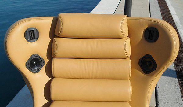 vista ravvicinata dello schienale di una poltrona in pelle color sabbia, con altoparlanti, e dietro vista del mare