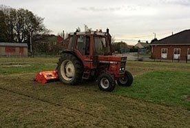 A red tractor at work on grass