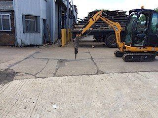 A yellow digger breaking up a concrete area