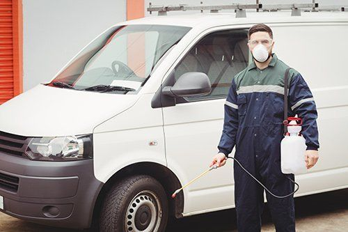 View of a Redwatch Solutions professional doing pest control at a commercial site