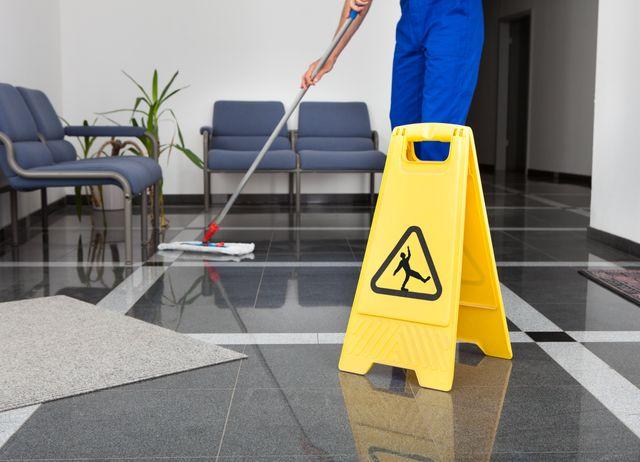 Immagine di una persona che sta pulendo il pavimento con un mocio, con di fronte un cartello per indicare il pavimento bagnato