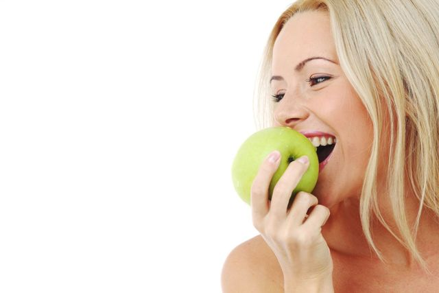 A woman enjoying an apple after receiving emergency dental care in Auckland