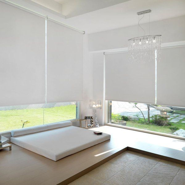 white roller blinds half drawn within a contemporary bedroom