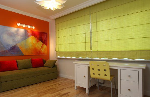 green roller blinds pulled down in a living space