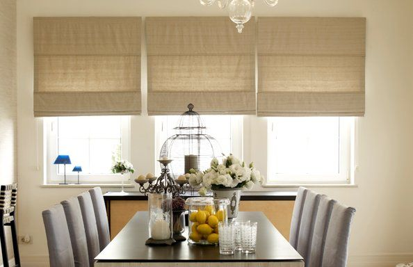 roller blinds hanging over 3 windows in a dining room