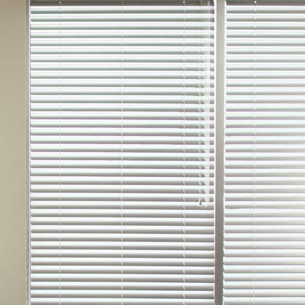 upvc white Venetian blind drawn over a window