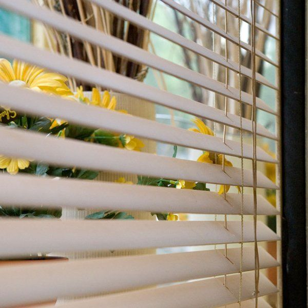 daffodils visible on a windowsill behind semi closed venetian blinds