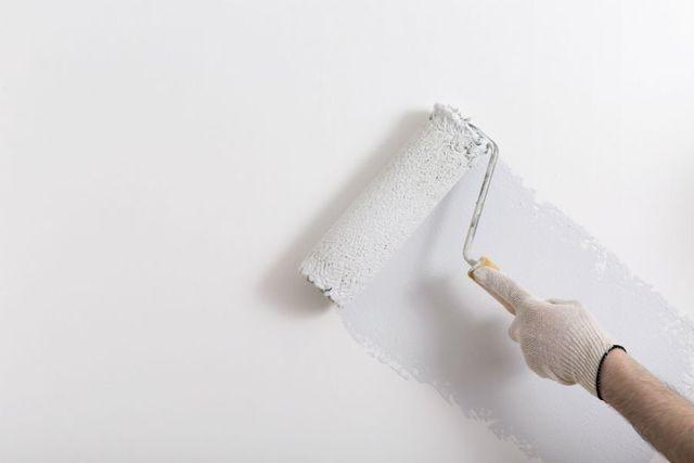 una mano con un rullo mentre imbianca una parete