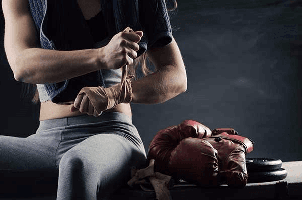 Woman boxer wrapping her wrists in Honolulu