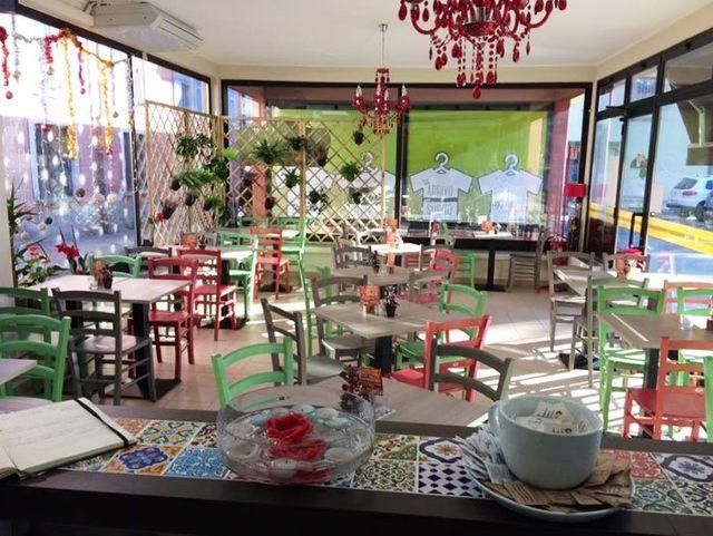 interno di Piada Mia con tavoli e sedie di color verde rosa e marrone, un traliccio in legno con delle piante
