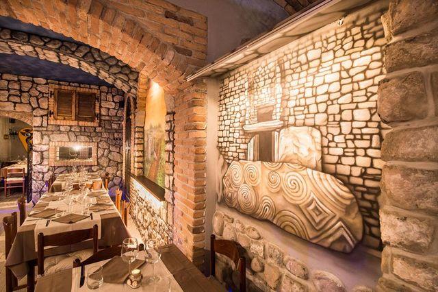 Dei tavoli apparecchiati all'interno di un ristorante con muri con mattoni a vista