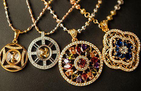 serie di pendenti con ciondoli grandi dorati, argentati con diamanti e rubini di diversi colori