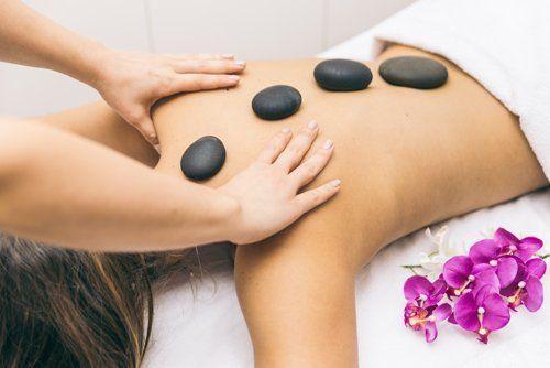 donna stesa e un'altra che le fa i massaggi con pietre