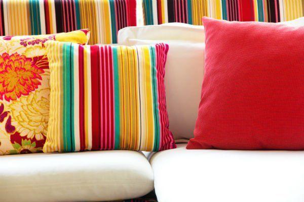 Sofà con l'arredamento di razze multicolore e cuscini di colori combinati