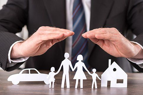 Concept of insurance with hands over a house, a car and a family in Waynesboro