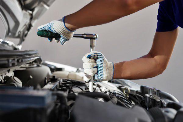 due mani con dei guanti che con un attrezzo stringono un bullone del motore di una macchina