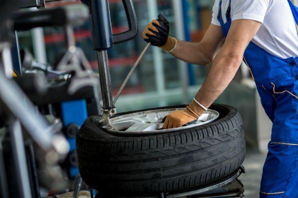 un gommista che con un macchinario inserisce un pneumatico nel cerchione