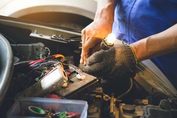 due mani che sistemano dei cavi elettrici della batteria di una macchina
