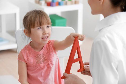 medico con una A in mano aiuta una bambina con la pronuncia