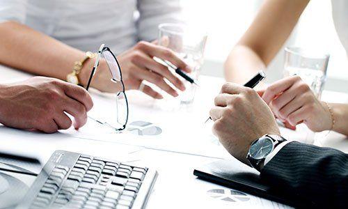 vista di alcune mani di persone con occhiali da vista in mano,bicchieri, una penna e vista di una tastiera di un computer
