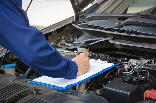 Uomo  che compila la scheda tecnica di un'auto, appoggiando la cartellina sul motore di una macchina