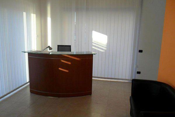una sala d'attesa con un banco reception ed un divanetto nero